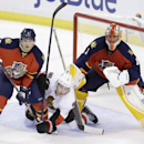 Ottawa Senators center Kyle Turris, center, is squeezed between Florida Panthers defenseman Dmitry Kulikov of Russia, left, and goalie Roberto Luongo during the third period of an NHL hockey game, Monday, Oct. 13, 2014 in Sunrise, Fla. The Senators defeat