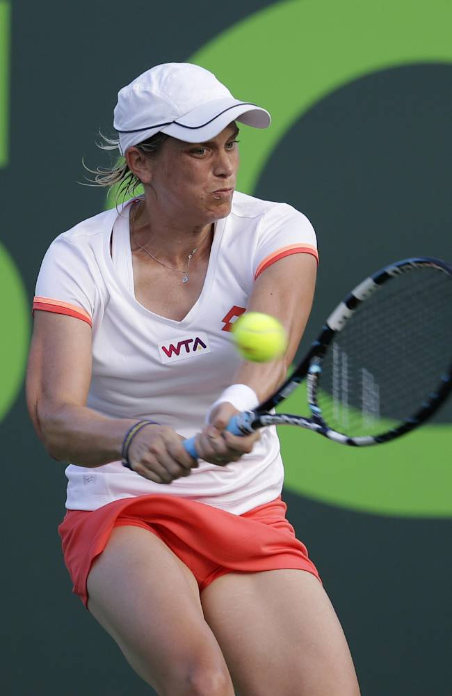 Romina Oprandi, of Switzerland, returns the ball to Agnieszka Radwanska, of Poland, at the Sony Open tennis tournament, Friday, March 21, 2014, in Key Biscayne, Fla