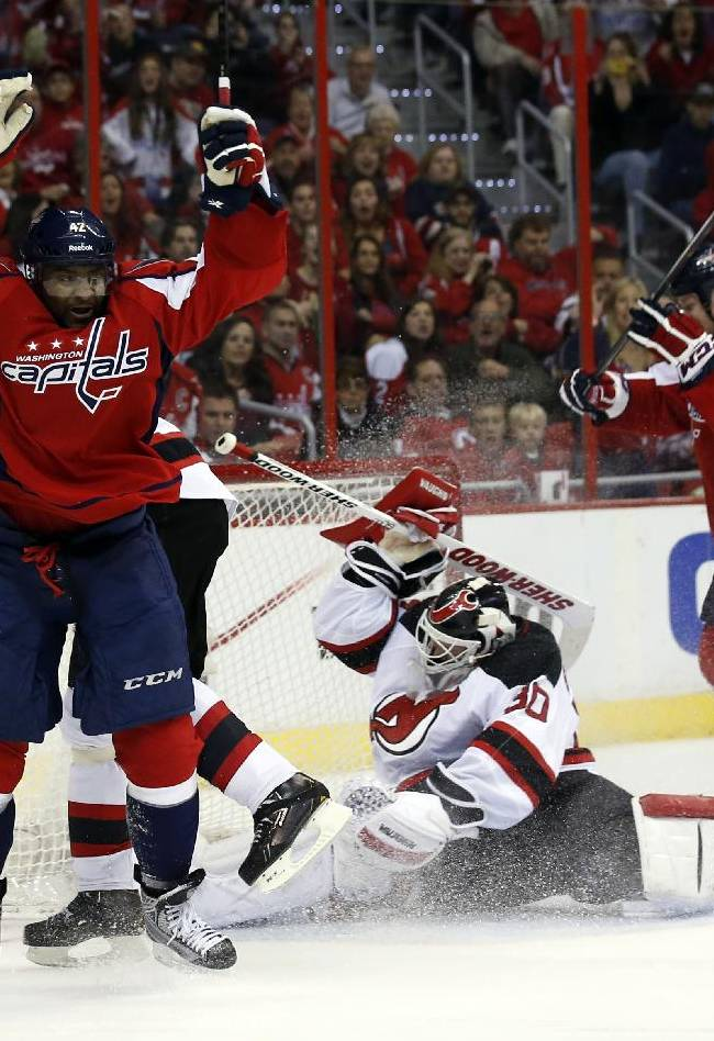 Washington Capitals right wing Joel Ward, left, celebrates his goal in front of New Jersey Devils goalie Martin Brodeur (30) in the second period of an NHL hockey game, Saturday, Dec. 21, 2013, in Washington