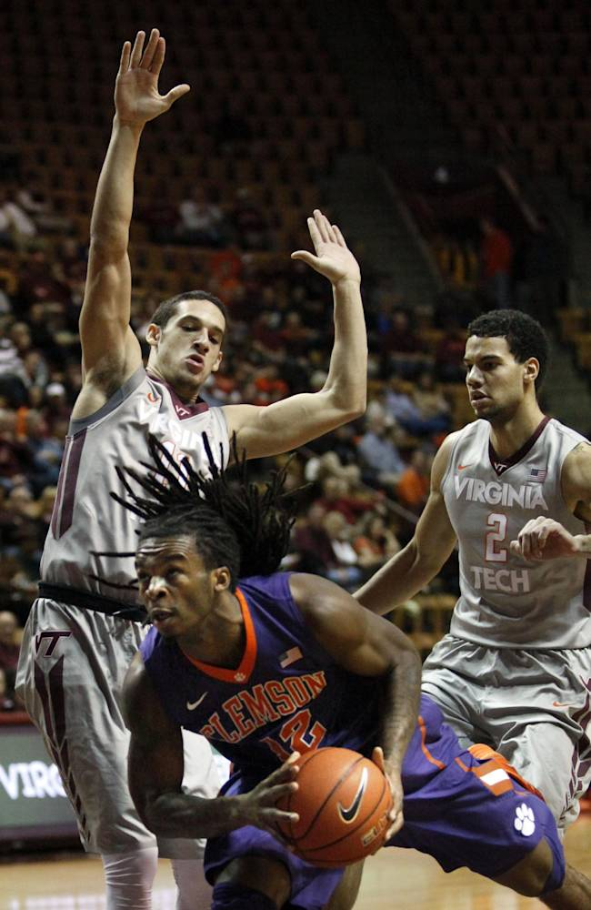Clemson's Rod Hall drives past the defense of Virginia Tech's Devin Wilson left, and Joey van Zegeren during the first half of an NCAA college basketball game in Blacksburg, Va., Wednesday, Jan. 15 2014
