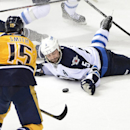 Winnipeg Jets defenseman Mark Stuart (5) passes the puck with his hand in front of Nashville Predators forward Craig Smith (15) in the third period of an NHL hockey game on Saturday, March 1, 2014, in Nashville, Tenn. The Jets won 3-1 The Associated Press