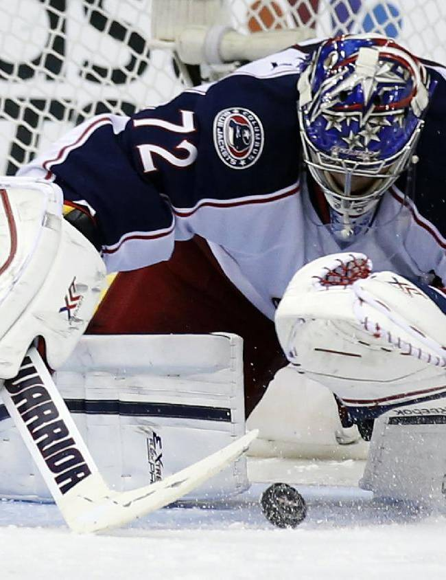 Columbus Blue Jackets goalie Sergei Bobrovsky, of Russia, reaches to cover the puck in the third period of an NHL hockey game against the Washington Capitals, Tuesday, Nov. 12, 2013, in Washington. The Capitals won 4-3 in overtime