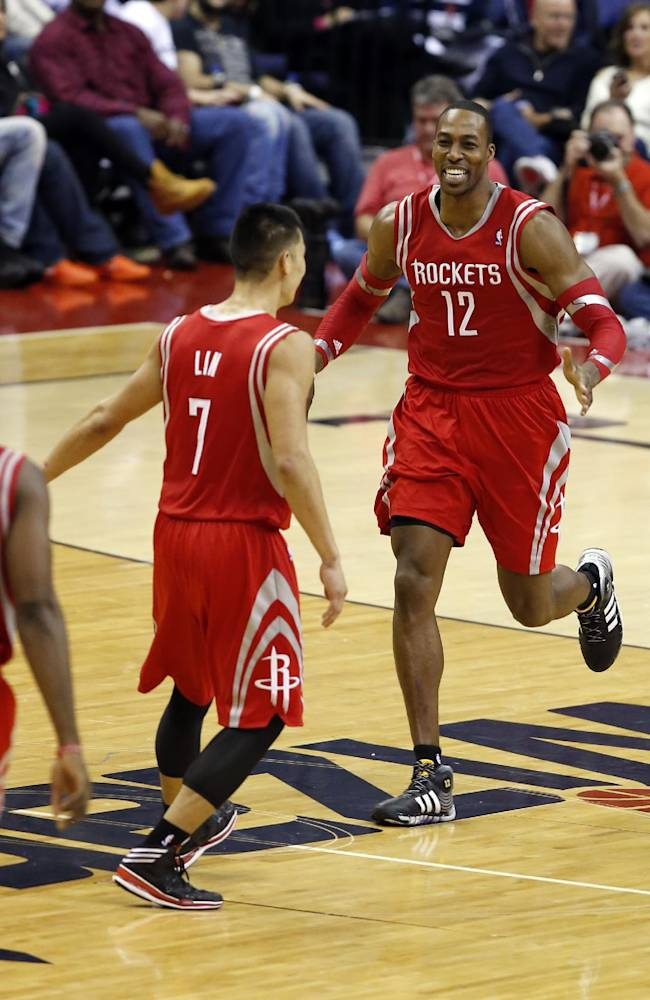 Houston Rockets forward Dwight Howard (12) celebrates his dunk with guard Jeremy Lin (7) during the second half of an NBA basketball game against the Washington Wizards, Saturday, Jan. 11, 2014, in Washington. The Rockets won 114-107