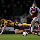 West Ham's James Tomkins, right, competes for the ball with Hull City's Shane Long during the English Premier League soccer match between West Ham and Hull City at Upton Park stadium in London, Wednesday, March 26, 2014