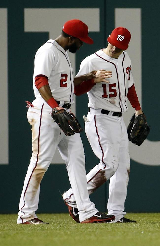 Washington Nationals center fielder Denard Span (2) looks at the injured right hand of left fielder Nate McLouth after McLouth caught a foul ball hit by Los Angeles Dodgers' Dee Gordon for an out during the eighth inning of a baseball game at Nationals Park, Tuesday, May 6, 2014, in Washington. McLouth was injured on the play and left the game. The Nationals won 4-0