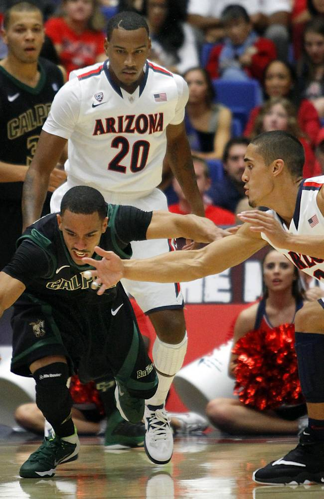 Cal Poly's Jamel Johnson, left, and Arizona's Nick Johnson scramble for a loose ball while Arizona's Jordin Mayes (20 looks on in the first half of an NCAA college basketball game, Friday, Nov. 8, 2013 in Tucson, Ariz