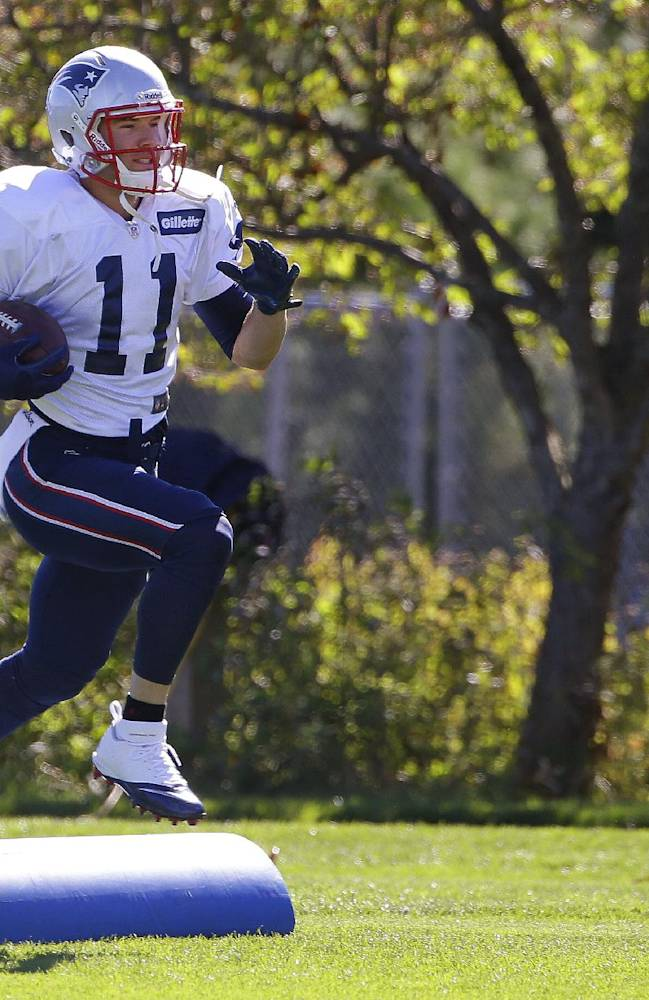 New England Patriots wide receiver Julian Edelman (11) carries a ball during a stretching and drills session before NFL football practice at the team's training facility in Foxborough, Mass., Wednesday, Sept. 18, 2013
