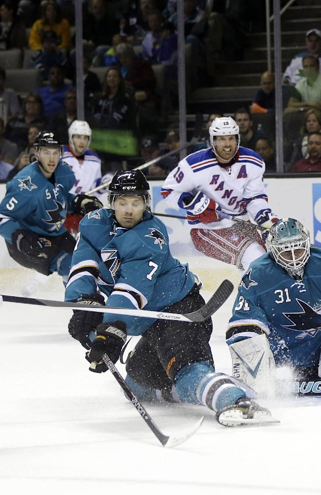 New York Rangers' Ryan Callahan (24) shoots next to San Jose Sharks' Brad Stuart (7) and Goalie Antti Niemi, right, of Finland during the second period of an NHL hockey game on Tuesday, Oct. 8, 2013, in San Jose, Calif