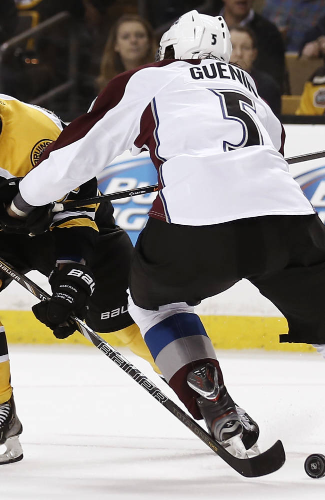 Boston Bruins' Brad Marchand tries to get around Colorado Avalanche defenseman Nate Guenin (5) during the second period of an NHL hockey game in Boston on Thursday, Oct. 10, 2013