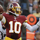Washington Redskins quarterback Robert Griffin III passes the ball during the first half of an NFL football preseason game against the New England Patriots in Landover, Md., Thursday, Aug. 7, 2014 The Associated Press