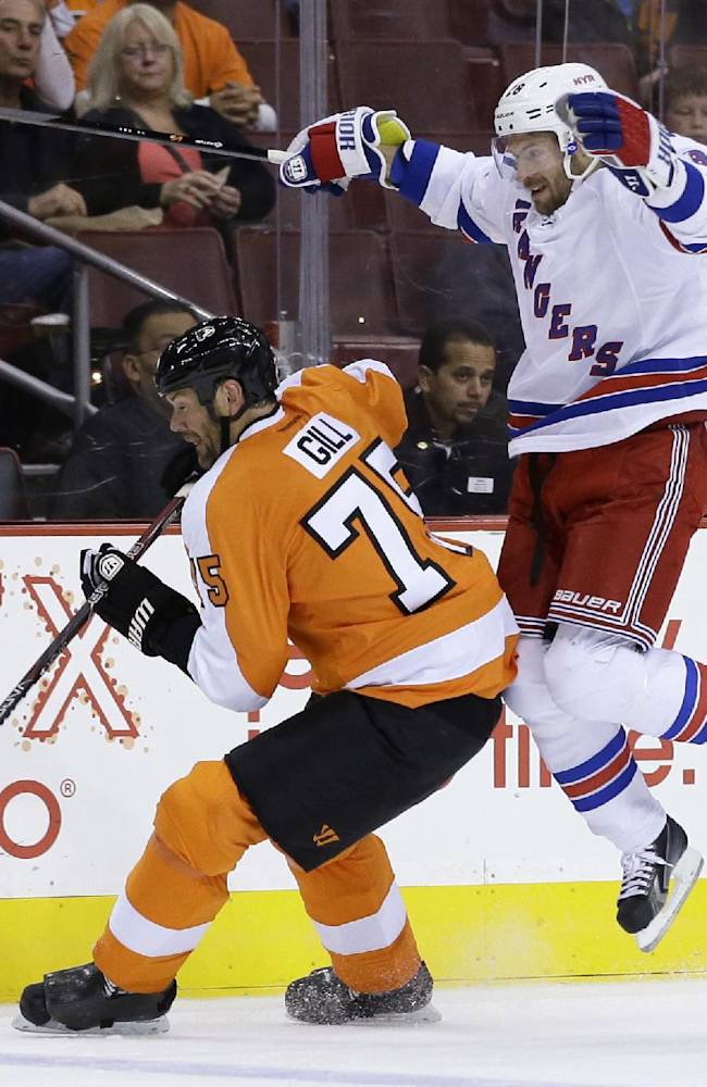 New York Rangers' Dominic Moore, right, collides with Philadelphia Flyers' Hal Gill during the first period of a preseason NHL hockey game, Tuesday, Sept. 17, 2013, in Philadelphia