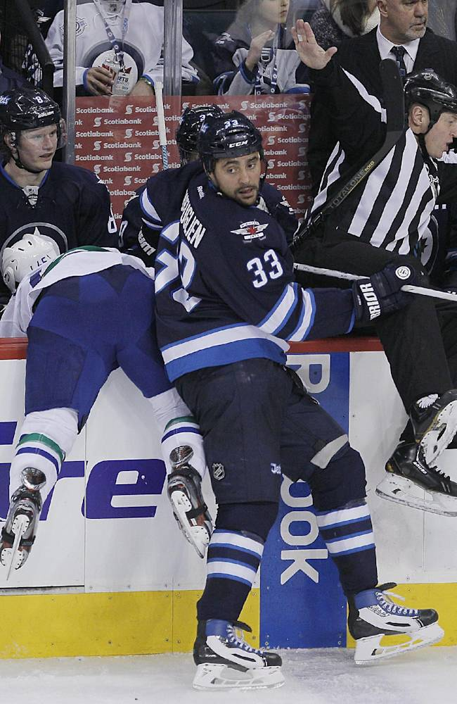 Vancouver Canucks' Jordan Schroeder (45) gets dumped over the boards by Winnipeg Jets' Dustin Byfuglien (33) during third period NHL action in Winnipeg on Friday, Jan. 31, 2014