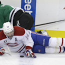 Montreal Canadiens center Tomas Plekanec (14) looks at the puck after crashing the boards with Dallas Stars defenseman Jason Demers (4) during the second period of an NHL hockey game Saturday, Dec. 6, 2014, in Dallas The Associated Press
