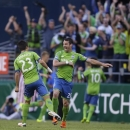 Seattle Sounders' Zach Scott, right, and Servando Carrasco, left, celebrate a goal scored by Sounders' Andy Rose (not shown) in the first half of an MLS soccer match against the Vancouver Whitecaps, Saturday, June 8, 2013, in Seattle. (AP Photo/Ted S. Warren)