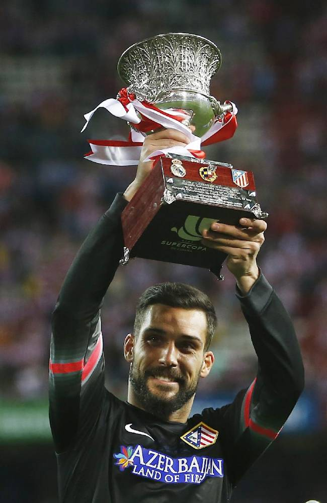 Atletico goalkeeper Moya celebrates the victory with the trophy during a Spanish Supercup second leg soccer match between Real Madrid and Atletico Madrid at Vicente Calderon stadium in Madrid, Spain, early Saturday, Aug. 23, 2014