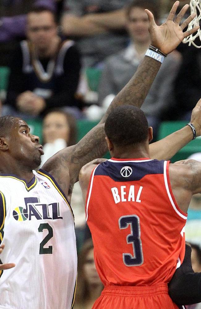 Utah Jazz's Marvin Williams (2) defends as Washington Wizards' Bradley Beal (3) drives to the basket during the first quarter of an NBA basketball game Saturday, Jan. 25, 2014, in Salt Lake City