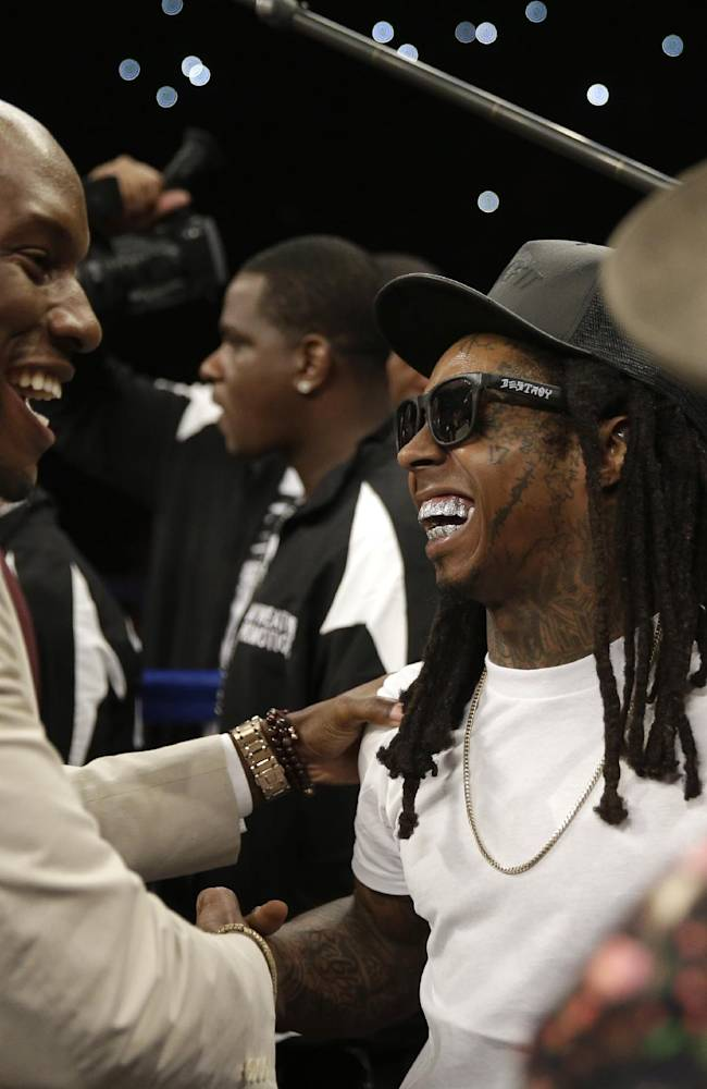 Tyrese, left, greets rapper Lil Wayne before the start of the WBC-WBA welterweight title boxing fight between Floyd Mayweather Jr. and Marcos Maidana Saturday, May 3, 2014, in Las Vegas