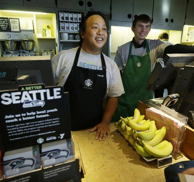 Baristas Truong Nguyen, left, and Ben Ruthruff, right, talk with customers near a display of special Seattle Seahawks Starbucks cards on Wednesday, Oct. 23, 2013, at a Starbucks store in Seattle. The Seahawks began a one-week fund-raising campaign Wednesday with Starbucks to benefit Seahawks head coach Pete Carroll's A Better Seattle program, which seeks to reach at-risk youth and prevent gang violence