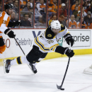 Boston Bruins' Johnny Boychuk (55) passes the puck as he is sent flying by Philadelphia Flyers' Scott Hartnell (19) during the second period of an NHL hockey game on Sunday, March 30, 2014, in Philadelphia The Associated Press