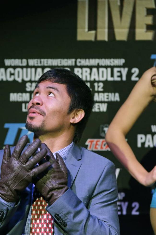 Boxer Manny Pacquiao, of the Phillipines, glances up at an air conditioning duct as he dons a pair of leather gloves while waiting to speak during a press conference Thursday, Feb. 6, 2014, in New York.  Pacquiao announced his WBO World Welterweight  title fight against defending champion Timothy Bradley, in Las Vegas, April 12, 2014. Bradley won their first encounter
