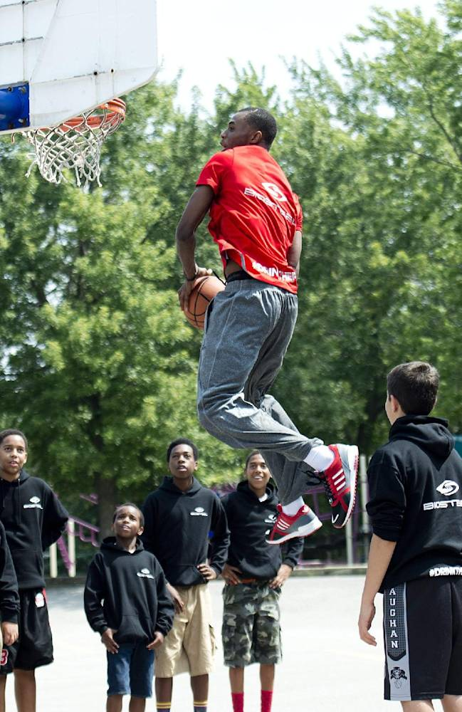NBA first-overall draft pick Andrew Wiggins, of Canada, goes up for a dunk while shooting a commercial with a bunch of kids after signing an endorsement deal with BioSteel Sports Drink at his old school in Concord, Ontario, Monday, Aug. 11, 2014