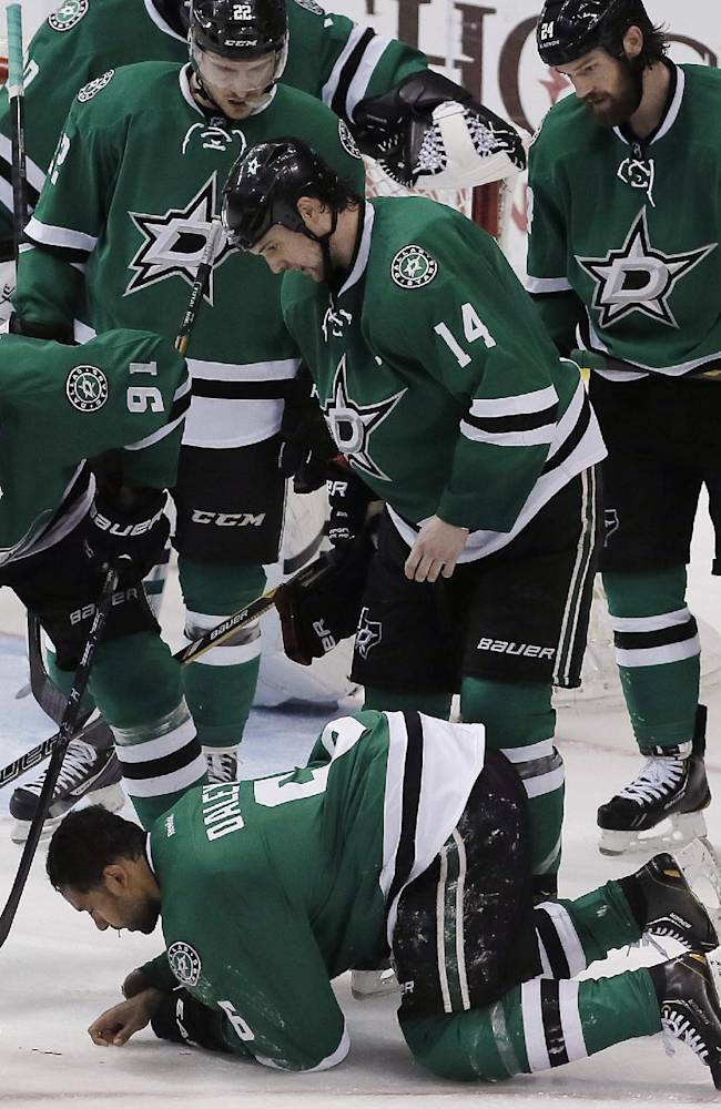 A Dallas Stars trainer rushes to assist defenseman Trevor Daley (6) who suffered a cut to his face during the third period of an NHL hockey game against the Columbus Blue Jackets, Wednesday, April 9, 2014, in Dallas. Columbus won 3-1