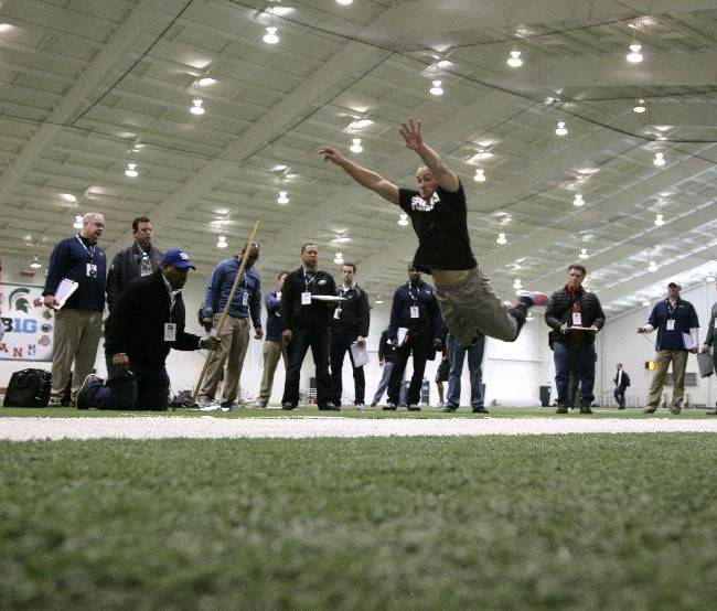 NFL scouts measure the long jump of former Michigan State linebacker Kyler Elsworth, Tuesday, March 11, 2014, in East Lansing, Mich