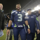 Seattle Seahawks quarterback Russell Wilson, middle, smiles as he walks off the field after an NFL divisional playoff football game against the Carolina Panthers in Seattle, Saturday, Jan. 10, 2015. The Seahawks on 31-17 The Associated Press