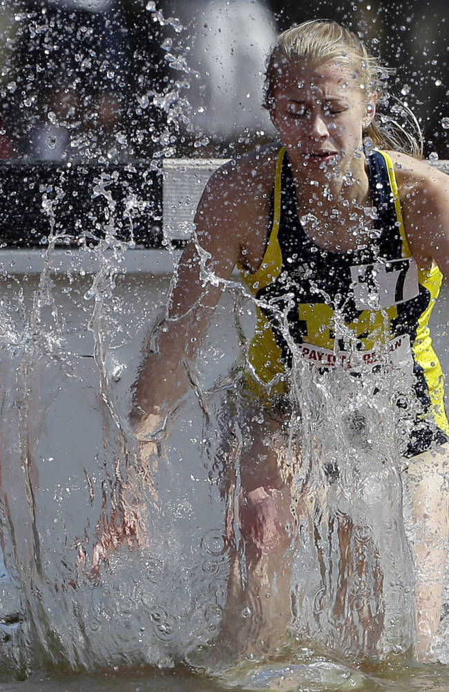 Michigan's Anna Pasternak splashes water as she competes in the 3,000m steeplechase during the Payton Jordan Invitational track and field meet on Sunday, May 4, 2014, in Stanford, Calif