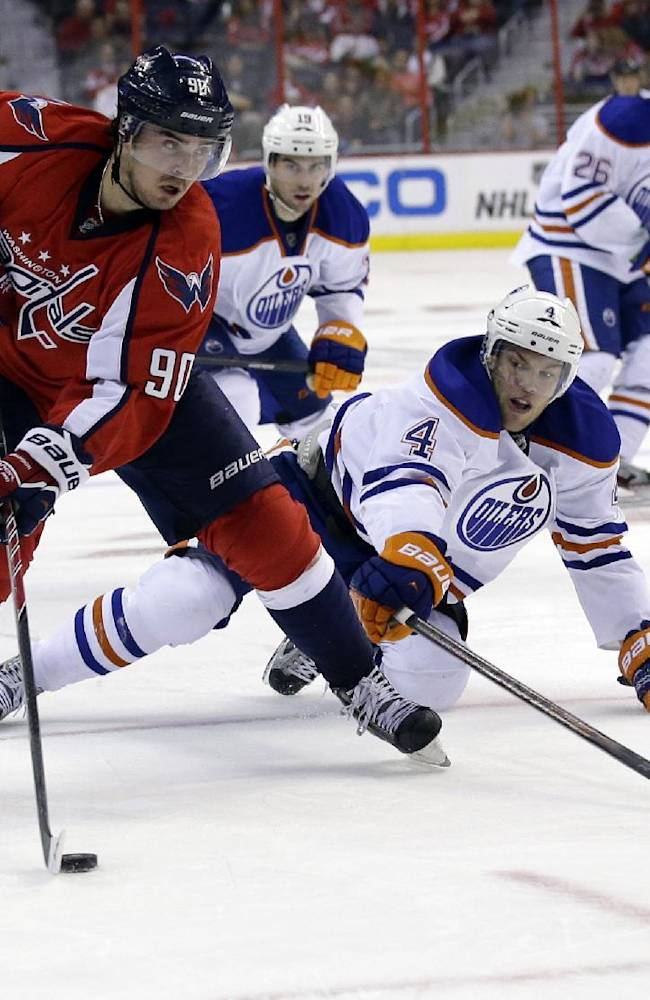 Washington Capitals center Marcus Johansson (90), from Sweden, looks to shoot as Edmonton Oilers left wing Taylor Hall (4) leans in to defend, in the third period of an NHL hockey game, Monday, Oct. 14, 2013, in Washington. The Capitals won 4-2
