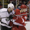 Los Angeles Kings' Jake Muzzin (6) ties up Detroit Red Wings' Andrej Nestrasil (49), of the Czech Republic, during the second period of an NHL hockey game, Friday, Oct. 31, 2014, in Detroit. The Red Wings defeated the Kings 5-2. (AP Photo/Duane Burleson)