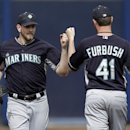 Seattle Mariners' James Paxton, left, and Charlie Furbush (41) fist-bump as they pass each other going and coming from the dugout to the bullpen in the fourth inning of an exhibition baseball against the San Diego Padres, Friday Feb. 28, 2014, in Peoria,