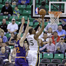 Utah Jazz's Derrick Favors (15) shoots as Phoenix Suns' Miles Plumlee (22) defends in the first quarter of an NBA basketball game on Wednesday, Feb. 26, 2014, in Salt Lake City The Associated Press