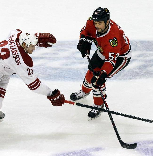 Phoenix Coyotes' Oliver Ekman-Larsson, left, and Chicago Blackhawks' Brandon Bollig battle for the puck during the third period of an NHL hockey game in Chicago, Thursday, Nov. 14, 2013. The Blackhawks won 5-4