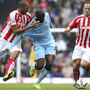 Stoke City's Steven N'Zonzi, left, and Charlie Adam, right, tackle Manchester City's Yaya Toure during their English Premier League soccer match at the Etihad Stadium, Manchester, England, Saturday Aug. 30, 2014