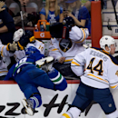 Buffalo Sabres' Nicolas Deslauriers, right, checks Vancouver Canucks' Ryan Stanton, left, into the Sabres' bench as, from left, Chad Ruhwedel, Christian Ehrhoff, of Germany, and goalie Matt Hackett get out of the way during second period NHL hockey actio