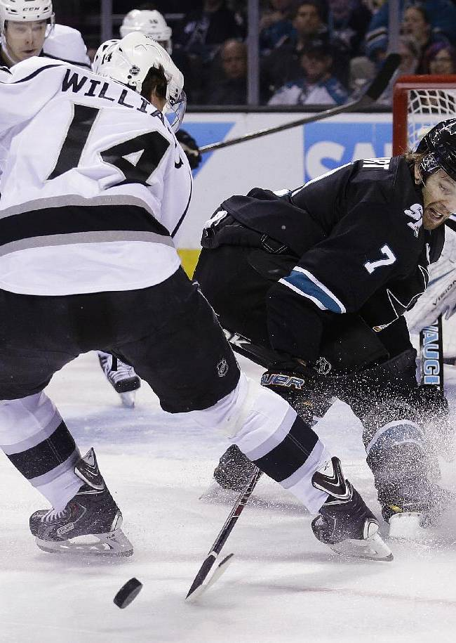 San Jose Sharks defenseman Brad Stuart (7) reaches for the puck between the skates of Los Angeles Kings right wing Justin Williams (14) during the second period of an NHL hockey game in San Jose, Calif., Thursday, April 3, 2014