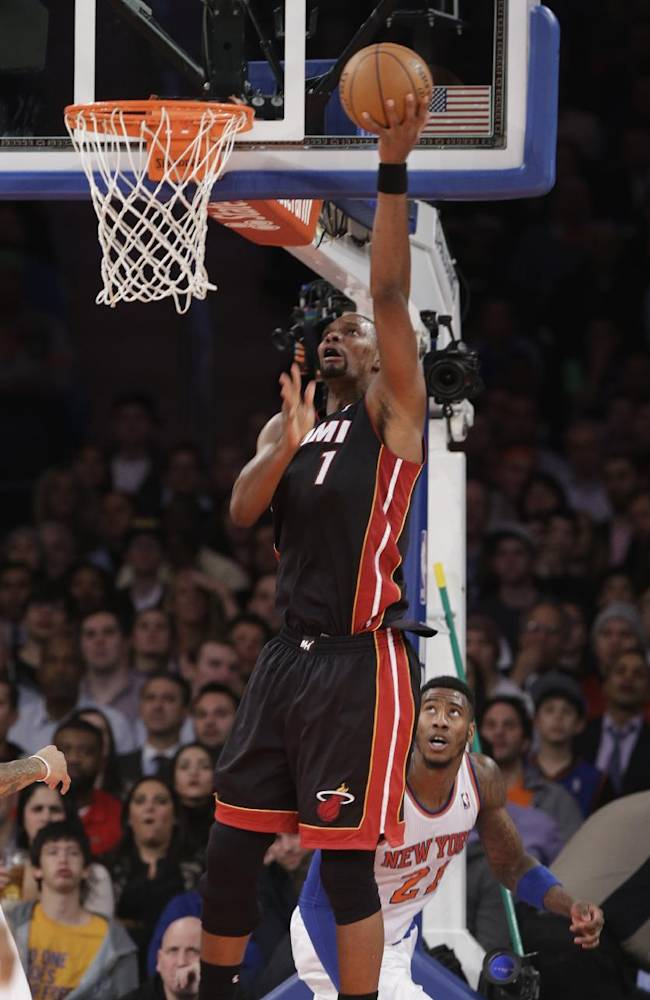 Miami Heat's Chris Bosh (1) scores in front of New York Knicks' Iman Shumpert (21) during the first half of an NBA basketball game on Thursday, Jan. 9, 2014, in New York