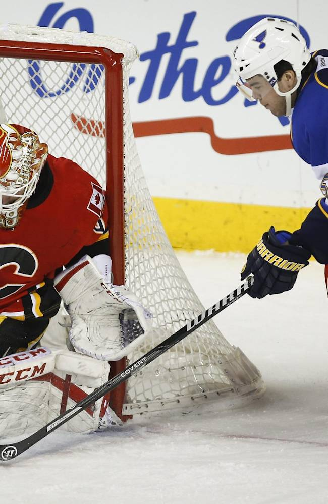 St. Louis Blues' Magnus Paajarvi, right, from Sweden, tries to get the puck past Calgary Flames goalie Reto Berra, from Switzerland, during first-period NHL hockey game action in Calgary, Alberta, Monday, Dec. 23, 2013