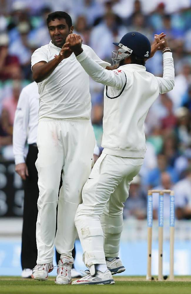 India's bowler Ravichandran Ashwin, left, celebrates after taking the wicket of England's Gary Ballance caught by Cheteshwar Pujara, right, during the second day of the fifth Test cricket match at Oval cricket ground in London, Saturday, Aug. 16, 2014