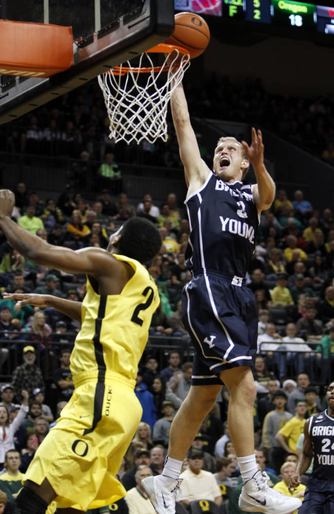 BYU's Tyler Haws, right, shots over Oregon's Damyean Dotson during the first half in an NCAA collage basketball game in Eugene, Saturday, Dec. 21, 2013