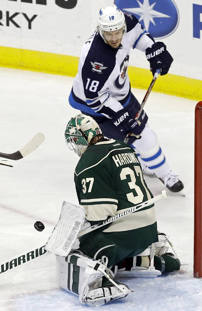 Winnipeg Jets' Bryan Little (18) races in for the rebound as Minnesota Wild goalie Josh Harding stops a shot in the first period of an NHL hockey game on Thursday, Oct. 10, 2013, in St. Paul, Minn