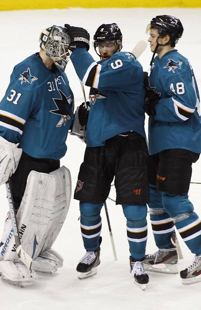 San Jose Sharks goalie Antti Niemi (31), left, celebrates with teammates Marty Havlat (9) and Tomas Hertl (48) after the Sharks beat the New Jersey Devils 2-1 in an NHL hockey game, Saturday, Nov. 23, 2013 in San Jose, Calif