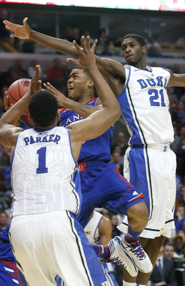 Kansas guard Frank Mason scores past Duke forward Jabari Parker (1) and Amile Jefferson during the second half of an NCAA college basketball game Tuesday, Nov. 12, 2013, in Chicago. Kansas won 94-83