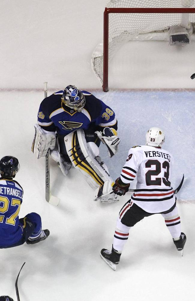 UPDATES WITH CHANGE IN SCORING - Chicago Blackhawks' Kris Versteeg (23) watches a goal by teammate Johnny Oduya get past St. Louis Blues goalie Ryan Miller and Blues' Alex Pietrangelo (27) during the first period in Game 1 of a first-round NHL hockey Stanley Cup playoff series Thursday, April 17, 2014, in St. Louis