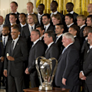 President Barack Obama holds up a medal given to him during an event honoring the Sporting Kansas City soccer team, Wednesday, Oct. 1, 2014, in the East Room of the White House in Washington, where he honored the 2013 Major League Soccer champions The Ass