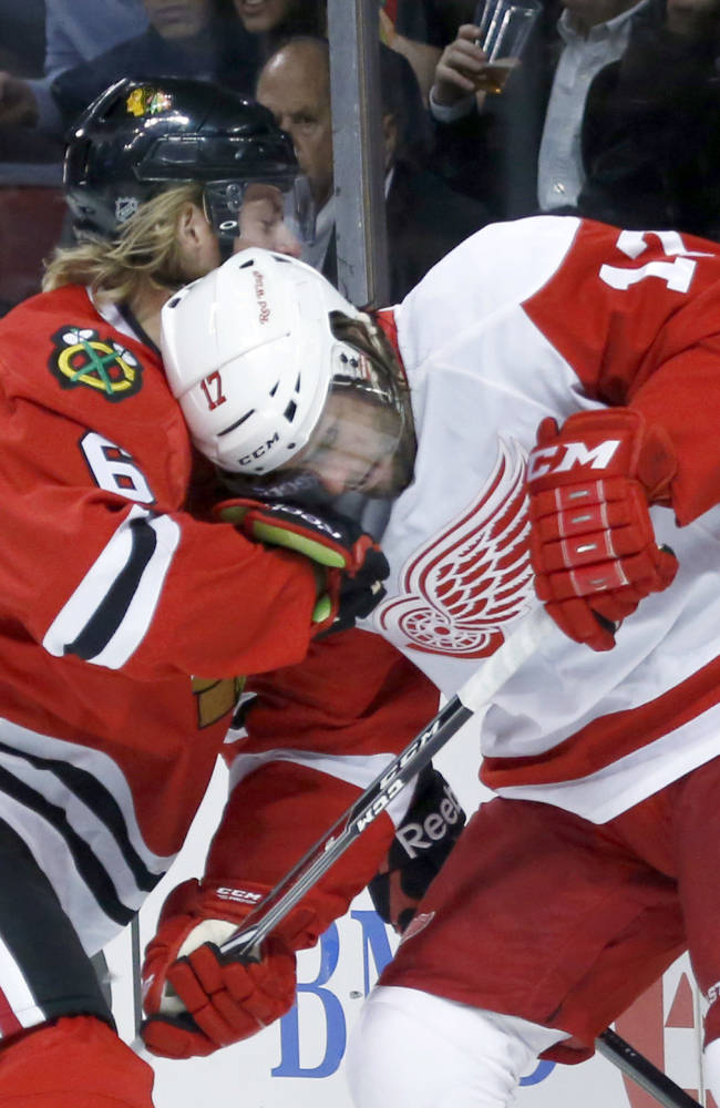 Chicago Blackhawks defenseman Mike Kostka (6) and Detroit Red Wings right wing Patrick Eaves battle for the puck behind the Blackhawks' net during the first period of an NHL preseason hockey game Tuesday, Sept. 17, 2013, in Chicago