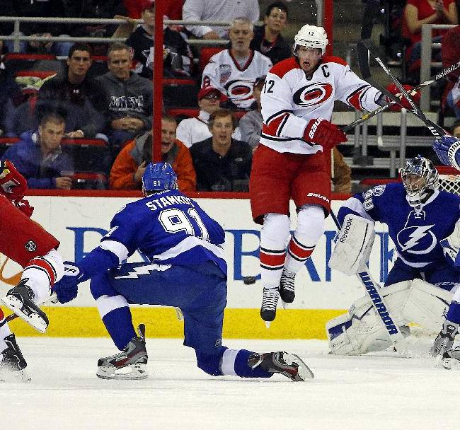 Carolina Hurricanes' Eric Staal (12) jumps to avoid the shot of teammate Andrej Sekera (4) of Slovakia,  as Tampa Bay Lightning's Steven Stamkos (91), Ryan Malone (12) and goalie Ben Bishop (30) defend during the first period of an NHL hockey game, Friday, Nov. 1, 2013, in Raleigh, N.C