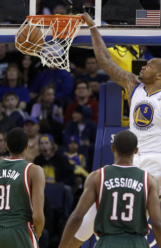 Golden State Warriors' Marreese Speights (5) scores as Milwaukee Bucks, from left, Giannis Antetokounmpo, John Henson (31), Ramon Sessions, and Khris Middleton watch during the first half of an NBA basketball game Thursday, March 20, 2014, in Oakland, Calif