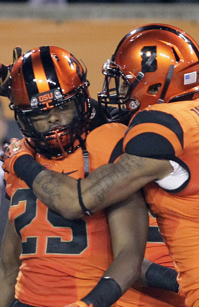 Oregon State defender Ryan Murphy is congratulated by teammate Tyrequek Zimmerman after Murphy scored on an interception during the first half of an NCAA college football game against Southern California in Corvallis, Ore., Friday, Nov. 1, 2013